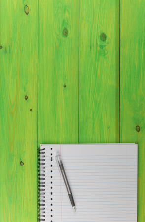Notepad and pen on a green wooden table