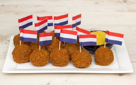 Dutch snack bitterballen with little dutch flags on a white plate