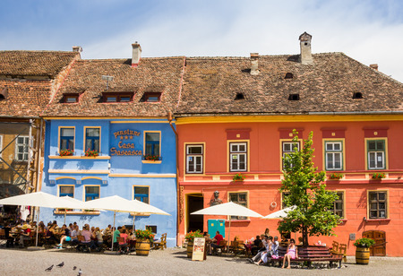 People eating and drinking at the central square  of Sighisoara, Romania