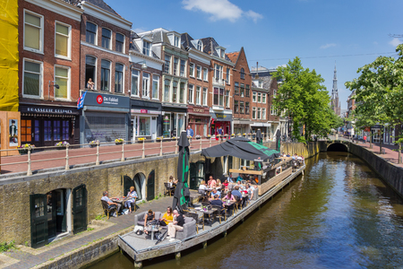 People sitting in the sun at a canal in Leeuwarden, Netherlands