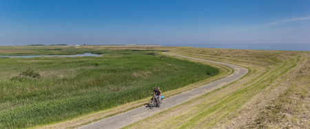 Panorama of a couple on bicycles along a dike on Texel island, Holland Stockfoto - 115436974