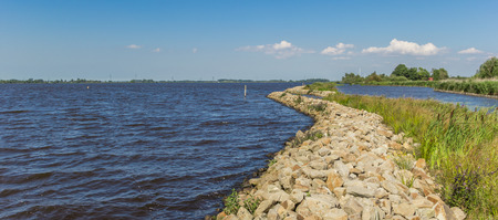 Panorama of a small dike at the Schildmeer lake in Groningen, The Netherlands Stock Photo