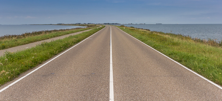 Road over a dike leading to Marken, Holland