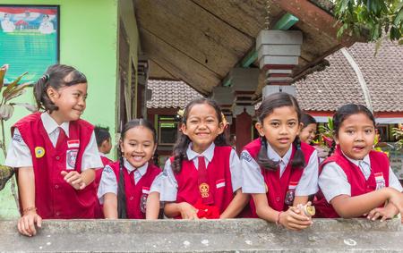 Indonesian schoolgirls in uniform posing in front of their school