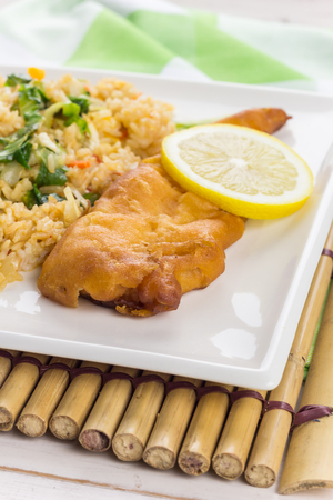 Fried cod with fried rice and vegetables on a bamboo placemat