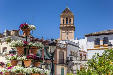 Colorful flowers in front of the church tower of Alcaudete, Spain