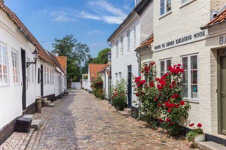Cobblestoned street with white houses in Ribe, Denmark