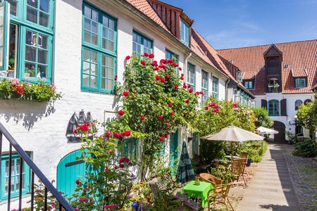 Colorful flowers at the facade of a white house in Flensburg, Germany