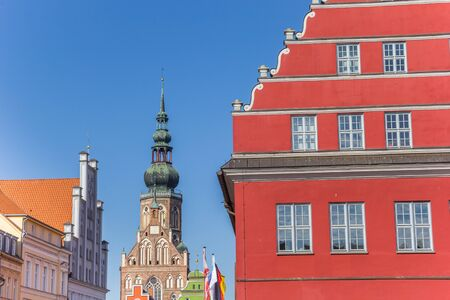Red town hall and church tower in Hanseatic city Greifswald, Germany