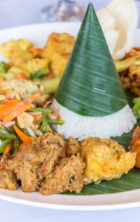 Nasi Campur Bali with tempeh, chicken and vegetables, served on a banana leaf Foto de archivo - 135468151