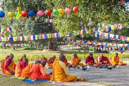 Monks in colorful clothing in the park of the Mayadevi temple of Lumbini, Nepal
