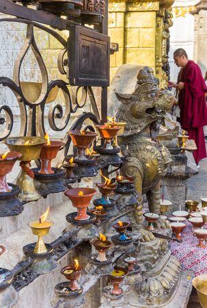 Candles and praying monk at the Swayambhunath temple in Kathmandu, Nepal