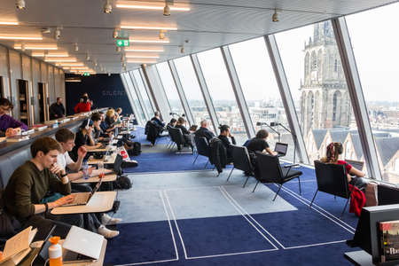 Students working in the library in the Groninger Forum with view over the Martini tower in The Netherlands Redactioneel
