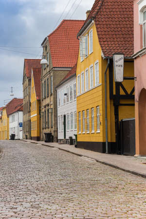 Cobblestoned street with colorful historic houses in Haderslev, Denmark