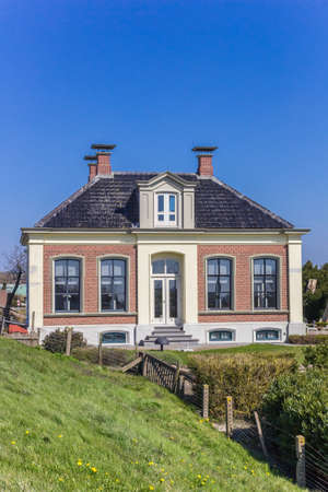 Historic house behind the dike in Zoutkamp, Netherlands