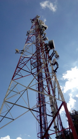 Telecommunication tower in the blue sky. Cellphone telecommunication tower with clouds and blue sky 写真素材