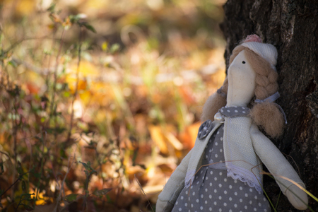 Tilda doll with two pigtails sits by the tree, on a blurred background. Handmade toy.