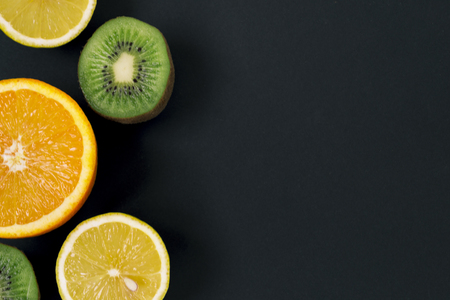 Slices of kiwi, lemon and orange on a black background, on a chalk board. There is a place for text. Round juicy orange