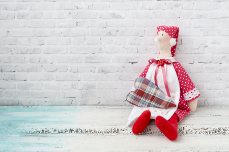 Tilda doll in a red cap, and in a red dress with four-piece. The doll sits on a wooden light table. The background is light brick. Handmade toy.
