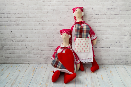 Tilda doll, soft toy with a heart, sitting on a wooden background. Handcraft concept. There is a place for text.