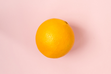 Isolated orange orange against a pink background. Vegetarianism, healthy lifestyle.