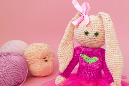 Knitted pink rabbit handmade. Easter bunny, in a pink knitted sweater and in a pink skirt. Sits among balls of yarn and pink flowers, On karalovom background. Banque d'images - 121660639