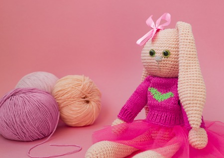 Knitted pink rabbit handmade. Easter bunny, in a pink knitted sweater and in a pink skirt. Sits among balls of yarn and pink flowers, On karalovom background.