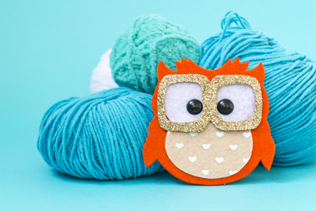 Self-made soft toy owl made of felt, on a color monophonic background. The owl stands next to the balls of yarn. There is a place for text. Hobby concept