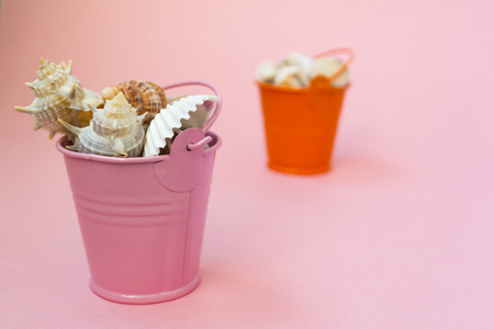 Two buckets filled with seashells on a pink background. Orange and pink bucket. There is a place for text. Maritime concept. Stock Photo