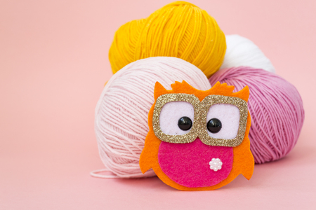 Self-made soft toy owl made of felt, on a color monophonic background. The owl stands next to the balls of yarn. There is a place for text. Hobby concept Stock fotó