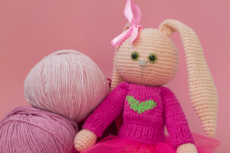Knitted pink rabbit handmade. Easter bunny, in a pink knitted sweater and in a pink skirt. Sits among balls of yarn and pink flowers, On karalovom background. Banque d'images - 122278824