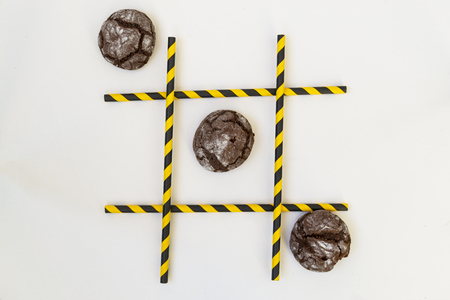 Three brown pastry cakes are in a row in a tic-tac-toe game, in a grid on a white background. The grid consists of colored tubes from a cocktail. Conceptual cooking and baking.