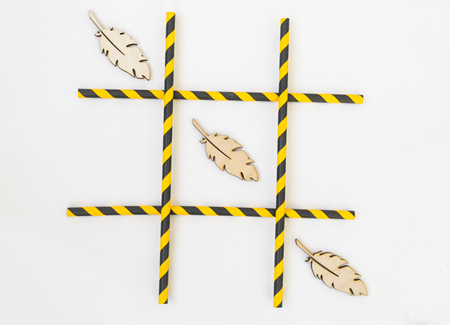 Three wooden bird feathers are lined up in a grid tic-tac-toe game on a white background. The grid consists of colored tubes from a cocktail. Boho style concept. 免版税图像