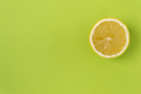 Round slice of yellow lemon, on a green background. There is a place of text.