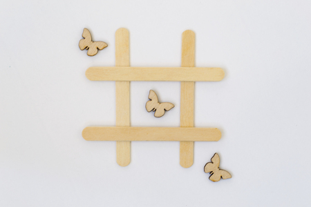 Three wooden butterflies lie in a row in the game of tic-tac-toe, in a grid on a white background. Concept summer.