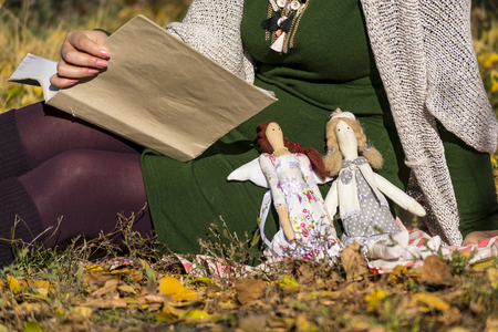 Two female tilde dolls in multi-colored dresses are sitting on the grass near the girl who is reading a thick book. Registration of holidays. Interior fairy doll handmade. Art and creativity.