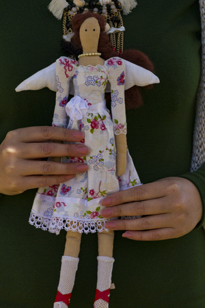 Female tilde doll in a multi-colored dress sitting on a female hand. Registration of holidays. Interior fairy doll handmade. Art and creativity.