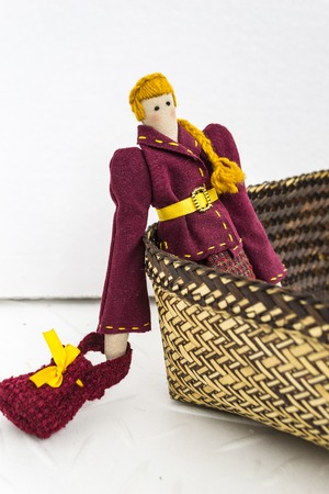 A female tilde doll in colorful clothes is sitting in a wicker basket on a white background. Registration of holidays. Interior fairy doll handmade. Art and creativity.