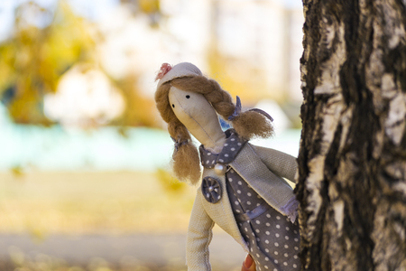 A female Tilda doll in a colorful dress looks out from behind a tree. Registration of holidays. Interior fairy doll handmade. Art and creativity. Blurred background, there is a place for text.