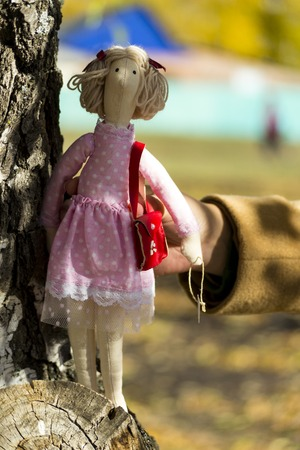 A female Tilda doll in colorful clothes is standing near a birch tree trunk. Registration of holidays. Interior fairy doll handmade. Art and creativity. Blurred background, there is a place for text.