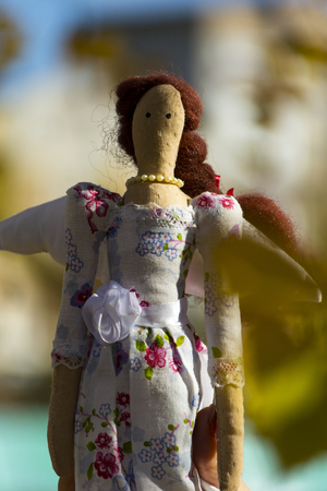 Female Tilda doll in colorful clothes closeup. Registration of holidays. Interior fairy doll handmade. Art and creativity. Blurred background,