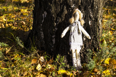 A female   doll in colorful clothes is standing near a birch tree trunk. Registration of holidays. Interior fairy doll handmade. Art and creativity.