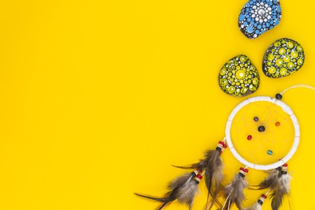 Dreamcatcher with brown bird feathers, and with threads and beads of rope hanging. Dreamcatcher handmade. It lies on a yellow background among the painted colored stones. There is a place for text.