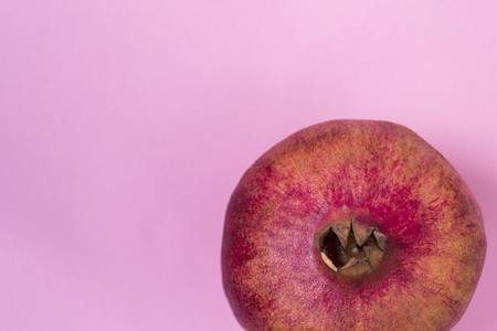 Whole red pomegranate isolated on pink background. There is a place for text. Healthy food concept.