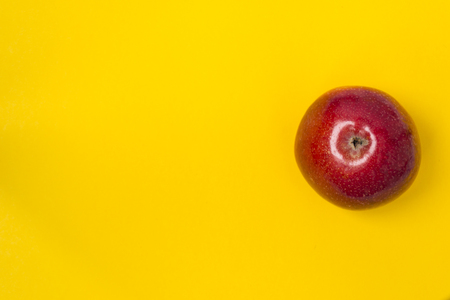 Fresh red apple on a plain yellow background. There is a place for text. Healthy food concept.