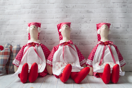 Three tilde dolls in red dresses, and white aprons, and red kalpaks sit on a light background. Interior dolls. There is a place for text. The concept of needlework, and handmade.