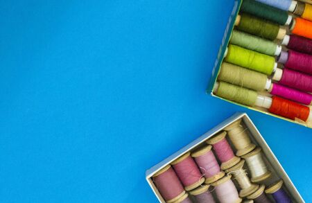 Colorful sewing threads lie in a box in a row gradient on a blue background, selective focus. There is a place for text.
