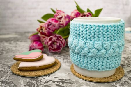 White cup of tea in a knitted blue case with pink flowers tulips and sweets, with gingerbread on a textural table. Spring, winter concept