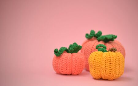 Autumn pink background with knitted pumpkins. Side view of knitted pumpkins of different sizes. Happy Thanksgiving Autumn Background. Autumn concept, there is a place for text.