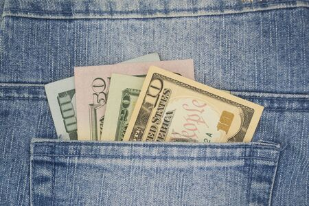 American money dollars in various denominations peep out of a jeans pocket. Business concept. 版權商用圖片 - 132121478